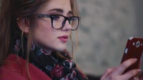 Jolie jeune femme textotant un message avec son téléphone Beauté naturelle, étant en ligne Réseaux sociaux, facebook L'écran banque de vidéos