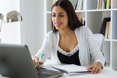 Jolie jeune femme travaillant avec l'ordinateur portable dans son bureau Image stock