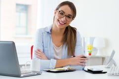 Jolie jeune femme travaillant dans son bureau Images stock