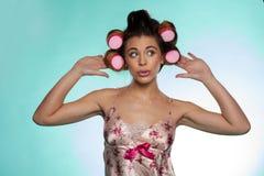 Jolie jeune femme vaine lui montrant des rouleaux de cheveux Photos stock