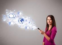 Jolie jeune fille retenant un téléphone avec les graphismes sociaux de medias Photo libre de droits