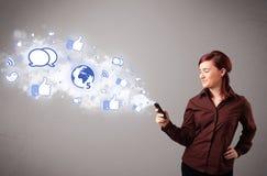 Jolie jeune fille retenant un téléphone avec les graphismes sociaux de medias Images stock