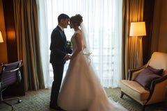 Jolie jeune mariée et marié asiatique étreignant la pièce de luxe Images stock