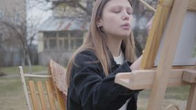 Jolie jeune peinture de tabagisme de fille de portrait sur la toile tout en se reposant dans l'arrière-cour dehors Artiste réussi banque de vidéos
