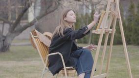 Jolie jeune peinture de tabagisme de fille sur la toile tout en se reposant dans l'arrière-cour dehors Artiste réussi passionné e banque de vidéos