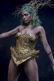Jolie, latine femme avec les cheveux verts et costume d'or avec le handma Images libres de droits