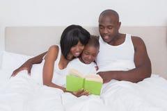 Jolie lecture de couples avec son fils dans le lit ensemble Photo stock