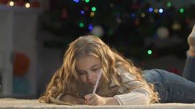 Jolie lettre d'écriture de fille à Santa, fermant ses yeux avec des mains aux cadeaux d'image clips vidéos