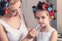 Jolie mère et sa fille ayant l'amusement avec le rouge à lèvres tandis que Image libre de droits