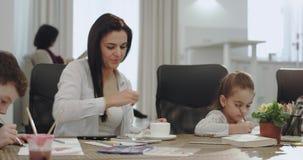 Jolie mère mûre avec beau travailler de trois enfants en ligne tout en faisant des devoirs avec ses enfants sur la cuisine clips vidéos