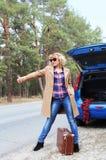 Jolie Madame faisant de l'auto-stop près de la voiture bleue Photographie stock libre de droits