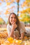Jolie Madame Lying sur les feuilles sèches avec le téléphone photos stock