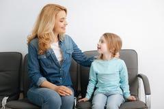 Jolie maman s'asseyant dans le hall avec sa fille photographie stock