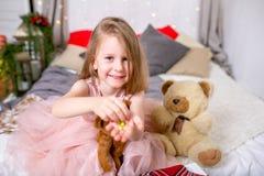 Jolie petite fille 4 années dans une robe rose Enfant dans la salle de Noël avec un lit, mangeant la sucrerie, le chocolat, les b image libre de droits
