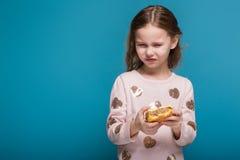 Jolie, petite fille dans le chandail avec la prise châtain de cheveux un hamburger Photographie stock libre de droits