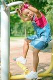 Jolie petite fille dans le costume de denim et jeux rouges de bandana sur le terrain de jeu des enfants images stock