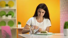 Jolie pilule de prise femelle avec de l'eau se reposant dans le restaurant d'aliments de préparation rapide, mangeant avec excès banque de vidéos