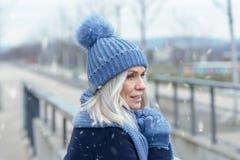 Jolie position blonde de femme dans la neige en baisse d'hiver images libres de droits