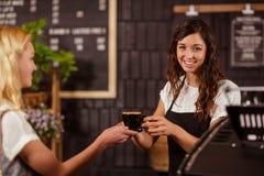 Jolie serveuse donnant la tasse de café au client image libre de droits