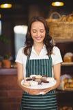Jolie serveuse montrant un plat des petits gâteaux Image stock