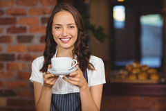 Jolie serveuse offrant une tasse de café image stock