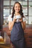 Jolie serveuse offrant une tasse de café photo libre de droits