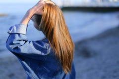 Jolie touriste de fille qui se tient sur le bord de la mer et développe des cheveux, en Photo stock