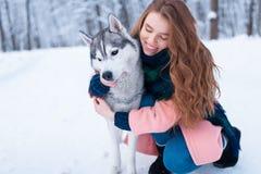 Jolies étreintes de femme avec le chien de traîneau sibérien Images stock