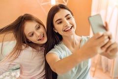 Jolies adolescentes ayant l'amusement tout en prenant des selfies Image stock