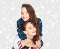 Jolies adolescentes de sourire étreignant au-dessus de la neige Images stock