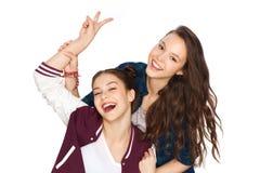Jolies adolescentes heureuses montrant le signe de main de paix Photographie stock