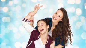 Jolies adolescentes heureuses montrant le signe de main de paix Image libre de droits