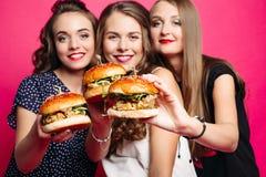 Jolies amies avec les hamburgers juteux Photos stock