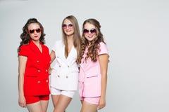 Jolies amies dans des lunettes de soleil et costumes à la mode au-dessus du petit morceau Photo libre de droits