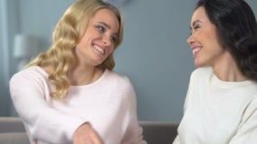 Jolies dames regardant l'un l'autre souriant, amitié femelle, réconciliation clips vidéos
