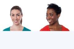 Jolies femmes de sourire au-dessus de blanc Photos stock