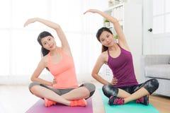 Jolies femmes de sourire regardant l'appareil-photo faisant le yoga Image stock
