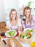 Jolies femmes mangeant d'une salade et buvant du vin Photos libres de droits