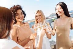 Jolies femmes positives buvant du vin mousseux Image libre de droits
