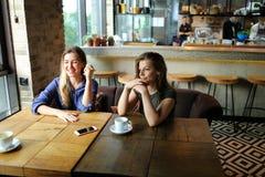 Jolies femmes positives s'asseyant au café avec des tasses de café et de sourire Photo libre de droits