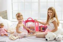 Jolies filles appréciant le jeu avec des poupées image libre de droits