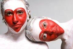 Jolies filles avec des formes rouges de coeur peintes par visages Photographie stock libre de droits