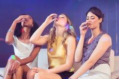 Jolies filles buvant l'alcool photographie stock