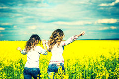 Jolies filles courant dans le domaine dans des chemises de broderie Photographie stock libre de droits