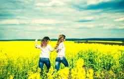 Jolies filles courant dans le domaine dans des chemises de broderie Images libres de droits