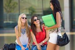 Jolies filles d'étudiant ayant l'amusement au campus Photo stock