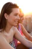 Jolies filles s'asseyant sur le toit au coucher du soleil Photographie stock libre de droits