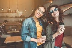 Jolies filles se tenant dans le cafétéria avec des tasses de boisson chaude Photos libres de droits