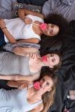 Jolies filles se trouvant sur le lit et mangeant des lucettes Photo libre de droits