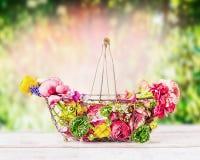 Jolies fleurs colorées dans le panier sur la table au fond vert de jour d'été, vue de face Photo stock
